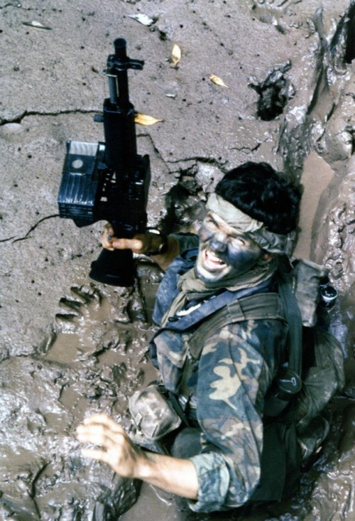 "Navy ""SEAL"" (Sea-Air-Land) Team Member moves through deep mud as he makes his way ashore from a boat, during a combat operation in South Vietnam in 1970. His gun is a Mk23 5.56mm Machine Gun (Stoner 63). Note his camouflage uniform & face paint. Photographed by PHC A. Hill."
